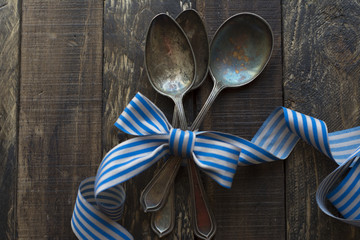 vintage metal spoons, ribbon and wooden background