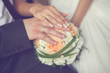 Bride and groom's hands with wedding rings and bouquet