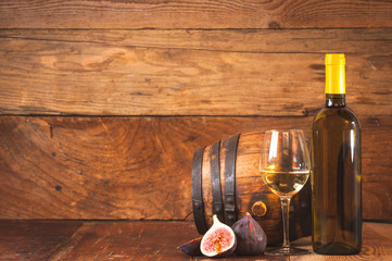 Barrel of white wine with bottle, glass and figs on a rustic tab