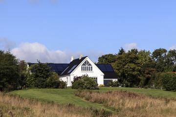 Grundstück mit Haus und großer Wiese unter blauem Himmel