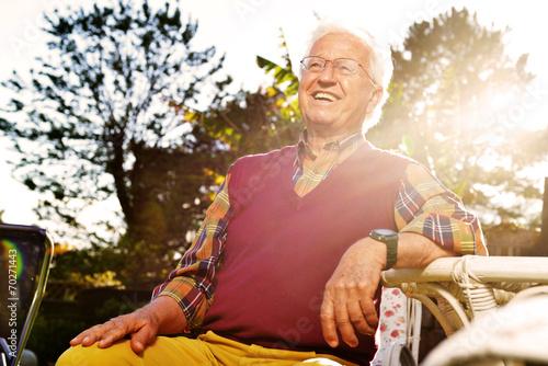 Fototapeta anziano seduto in giardino al tramonto