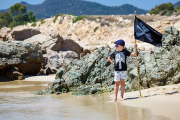 Cute boy dressed as pirate on beach