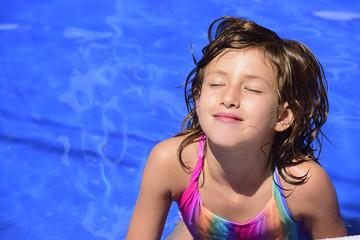 Happy kid relaxing in the pool