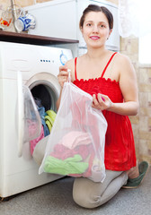 girl in red dress loading the washing machine