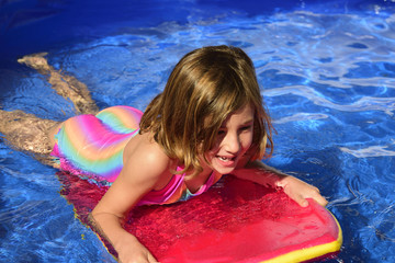 Happy little surfer girl with surf board