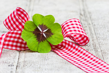 vierblättriges Kleeblatt in Geschenkschleife auf Holz