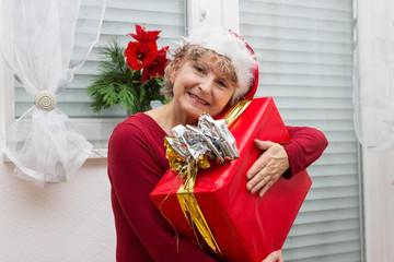 Seniorin mit Nikolausmütze und Geschenk