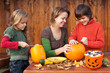 Woman helping kids to carve their Halloween jack-o-lantern