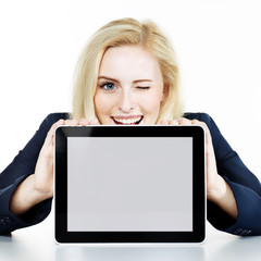 Woman winking over her tablet pc with copyspace