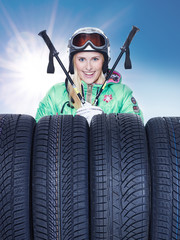 Woman with skiing gear and winter tyres