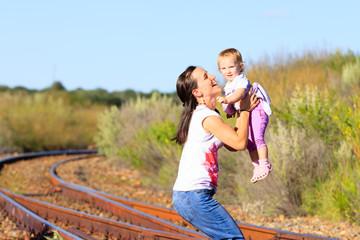 Mutter mit Kleinkind auf Bahngleisen