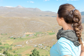 Girl looks the plateau of Campo Imperatore Abruzzo, Italy