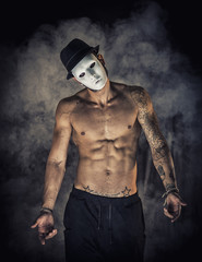 Shirtless man dancer or actor with creepy, scary mask