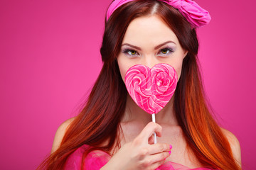 Beautiful redheaded girl with a large candy on a pink