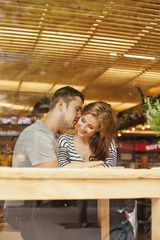 lovely couple sitting indoors in cafe (view through the glass)