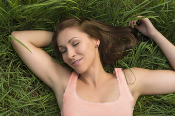 Happy woman sleeping in meadow