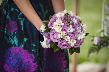 Beautiful bouquet of purple roses in their hands