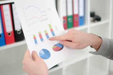 Man's finger showing business graphs