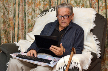 Old man working with laptop computer at home