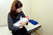Worried mother holds her sick baby in hospital ward room.