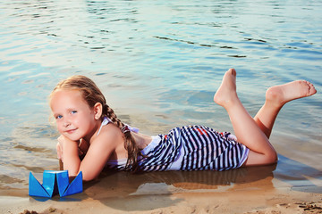 Cute little girl playing origami boat. Toned image