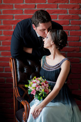 Bride and groom kissing on a red wall background
