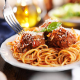 eating a plate of spaghetti and meatballs with fork