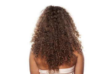 rear view of a young woman with a long curly hair