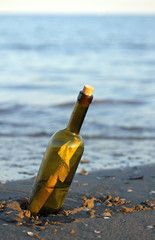bottle with a secret message on the shore of sandy beach