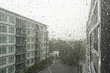 Drops of rain on a window pane, buildings in background. - 70288472