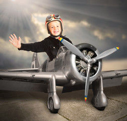 Happy little pilot in retro aircraft.