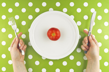 Woman eating fresh red tomato, top view