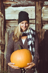 Cute woman holding autumn pumpkin