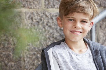 Portrait of young boy smiling at camera, outdoors.