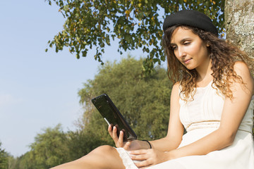 Attractive young woman reading a tablet under a tree