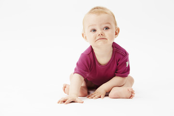 Baby girl looking away against white background.