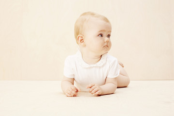 Baby girl looking away, studio shot.