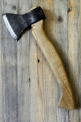 ax with oak handle on a wooden background, vertical