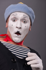 Portrait of young male mime with white face, grey hat showing em