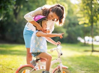 Mother wearing helmet on baby girl on bicycle