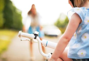 Closeup on baby girl sitting on bicycle