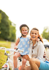 Portrait of smiling mother and baby girl sitting on bicycle