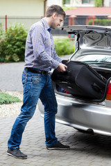 Man putting luggage into car trunk
