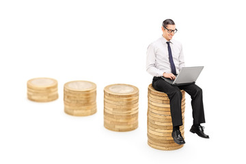 Man working on laptop seated on a pile of coins