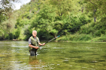 Senior man fishing in a river on a sunny day