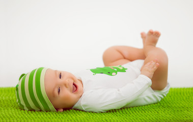 Smiling baby in a hat lying on the green soft carpet