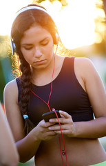 Young girl listening to music with mobile phone.