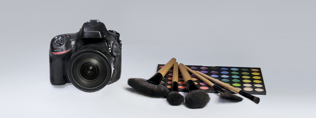 Камера и кисти для макияжа на сером фоне