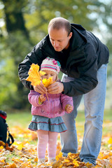 Man with a daughter collect fallen list in Park