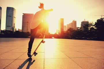 woman skateboarder skateboarding at sunrise city